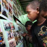 Follow up children (former street children) looking at 10 year photo exhibition